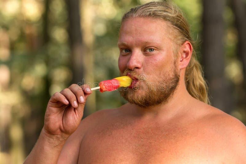 O homem está comendo o gelado foto de stock