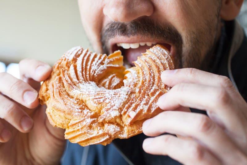 O homem está comendo um anel do creme - uma sobremesa tradicional do russo imagens de stock royalty free