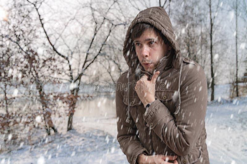 O homem está congelando-se fora no inverno frio foto de stock