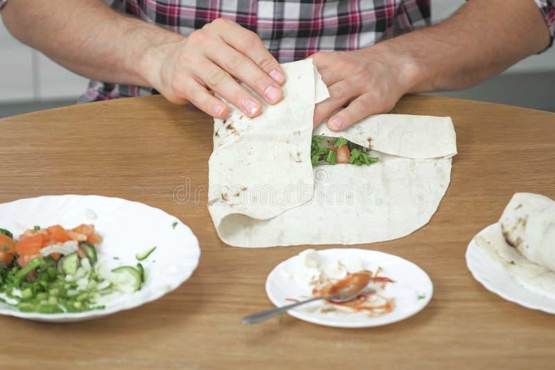 O homem está cozinhando o shawarma na mesa de cozinha em casa Pão árabe, vegetais e cebola verde com molho e maionese fim fotos de stock