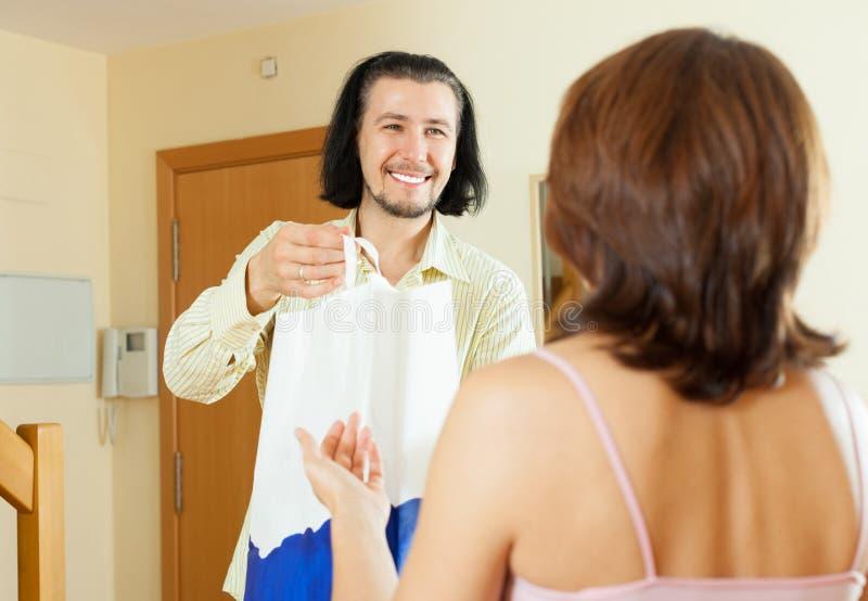 O homem está dando um presente surpreendente às mulheres em casa fotografia de stock royalty free