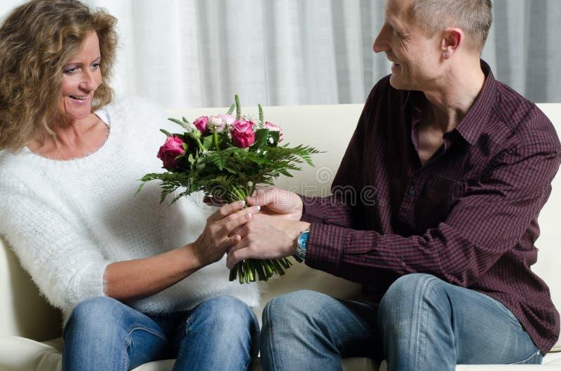 O homem está dando um ramalhete das flores à mulher fotos de stock royalty free