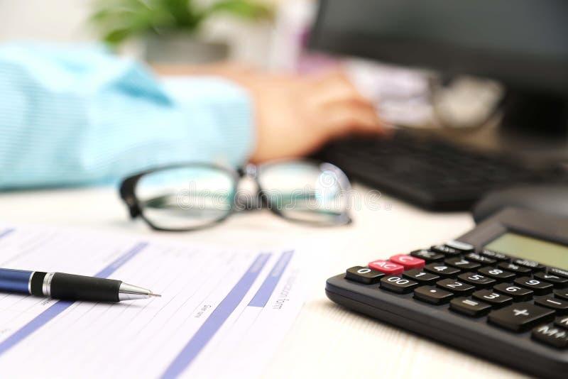 O homem está datilografando no teclado Imagem do formulário de candidatura, da pena, da calculadora e dos vidros foto de stock royalty free