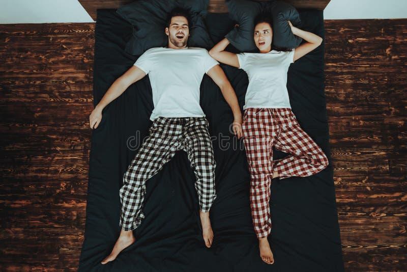 O homem está dormindo e ressona na cama com mulher foto de stock royalty free