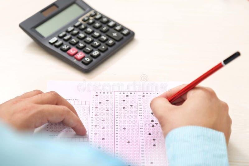 O homem está enchendo a folha do OMR com o lápis Imagem da calculadora na tabela fotografia de stock royalty free