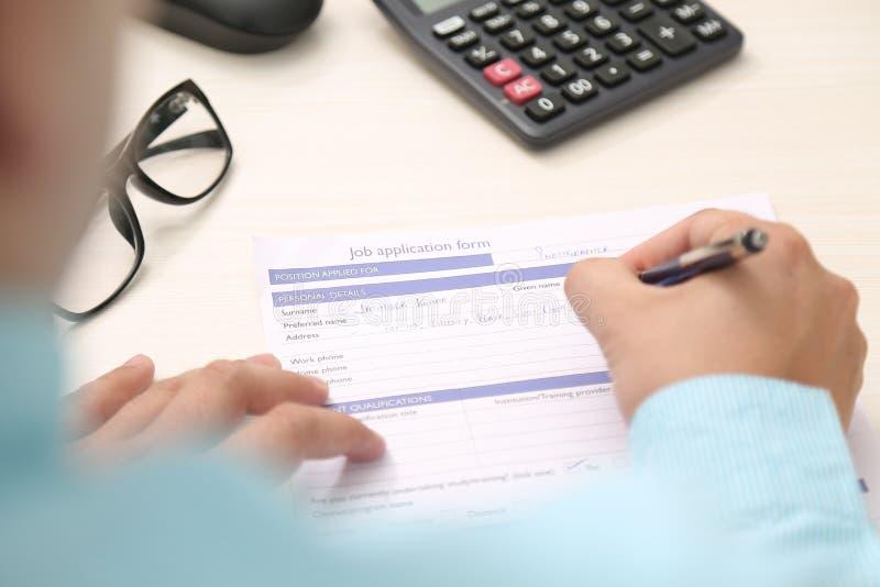 O homem está enchendo o formulário com a pena Imagem da calculadora e dos vidros na tabela foto de stock royalty free
