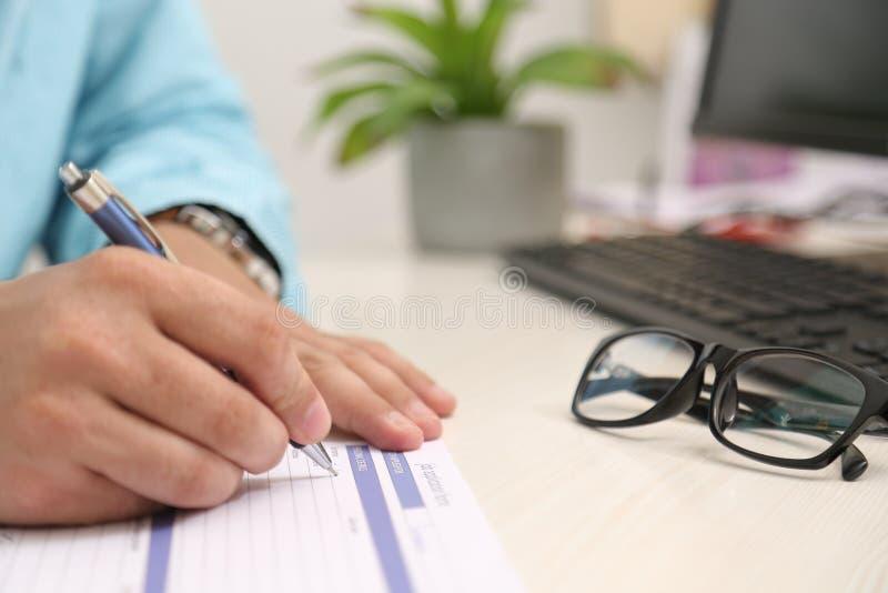O homem está enchendo o formulário com a pena Imagem do potenciômetro de flor, do computador, do teclado e dos vidros na tabela imagens de stock