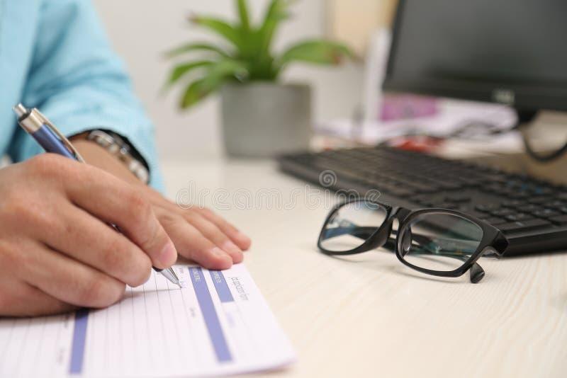 O homem está enchendo o formulário com a pena Imagem do potenciômetro de flor, do computador, do teclado e dos vidros na tabela fotos de stock royalty free