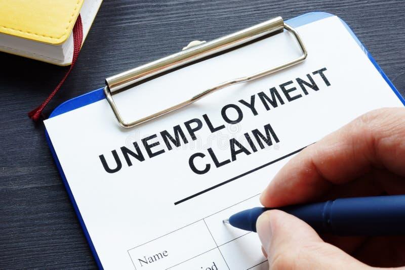 O homem está enchendo-se no formulário de reclamação do desemprego imagem de stock