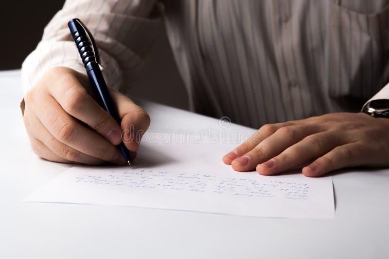 O homem está escrevendo em uma folha de papel fotografia de stock royalty free