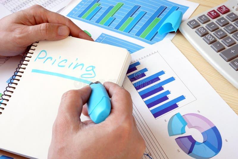 O homem está escrevendo a fixação do preço da palavra em uma nota imagem de stock