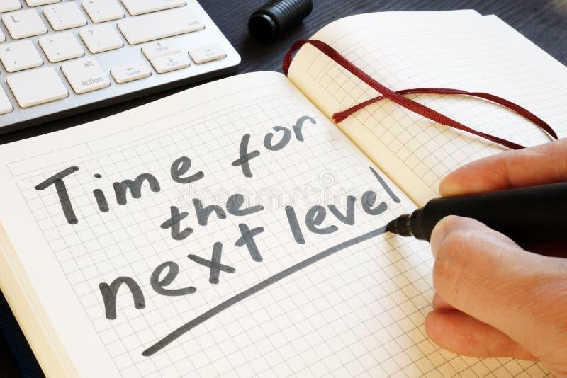 O homem está escrevendo a hora para o nível seguinte motivation fotos de stock royalty free