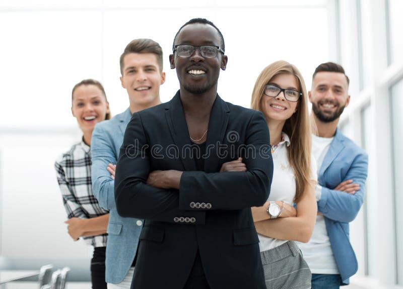 O homem está estando com seus braços cruzados com sua equipe fotografia de stock royalty free