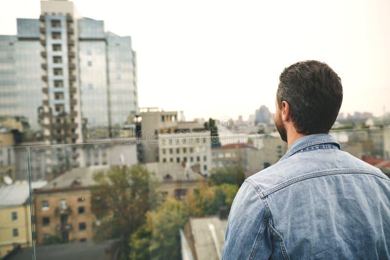 O homem está estando exterior e está olhando na cidade foto de stock royalty free