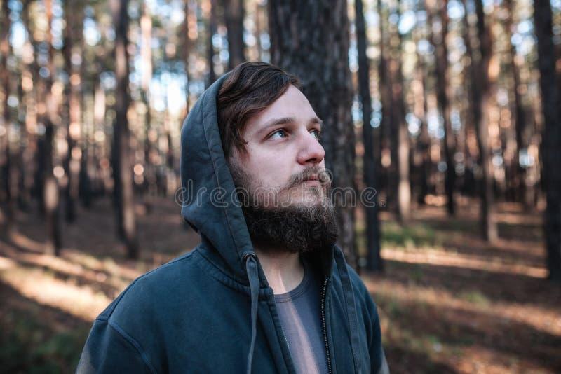 O homem está estando na floresta e apenas no relaxamento vestido como homies na obscuridade - goodie azul fotos de stock royalty free