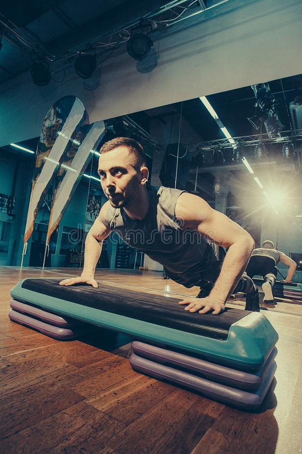O homem está exercitando seus pés no deslizante Exercício dos braços Imagem tonificada imagem de stock
