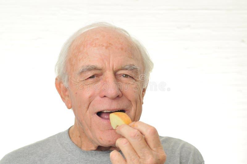 O homem está feliz comendo uma fatia de maçã imagem de stock royalty free