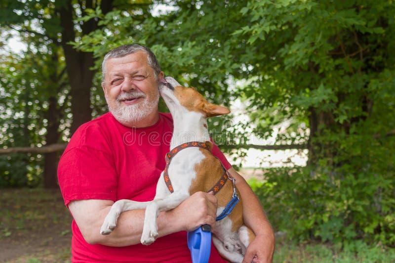 O homem está feliz quando seu animal de estimação mostra a afeição foto de stock