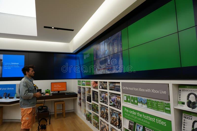 O homem está guardando jogos Xbox do controlador um Microsoft interno imagem de stock