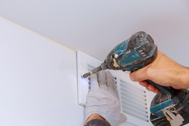 O homem está guardando a mão fura nas mãos O trabalhador que instala o respiradouro do banheiro da parede trabalha a renovação no fotos de stock royalty free