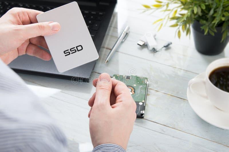 O homem está guardando o disco do SSD fotos de stock