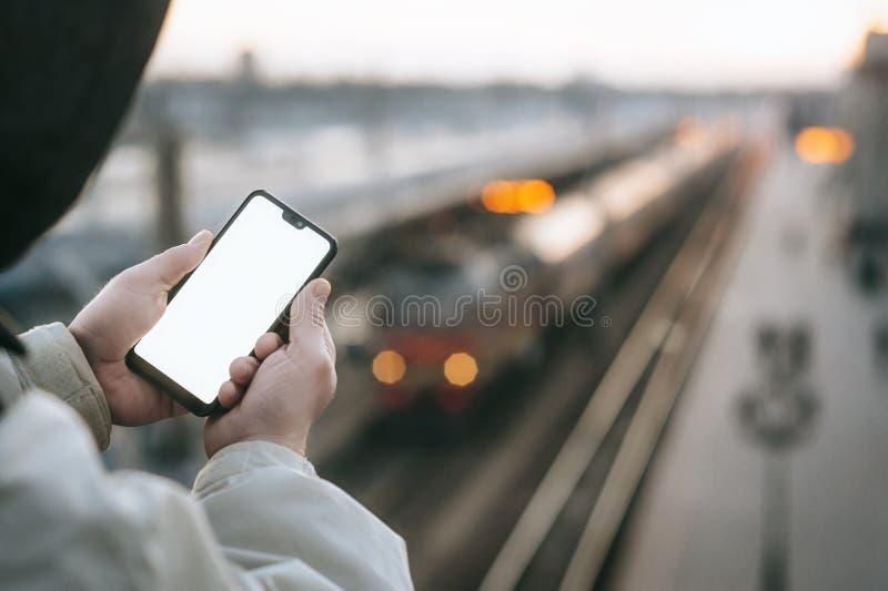 O homem está guardando um smartphone ascendente trocista em sua mão, na perspectiva do trem na estação de trem imagens de stock royalty free