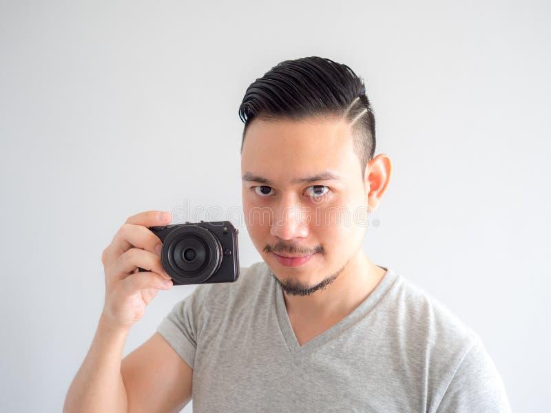 O homem está guardando uma câmera mirrorless e tenta-a tomar uma foto fotos de stock royalty free