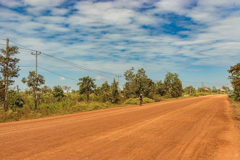 O homem está montando a bicicleta na área rural em Camboja foto de stock