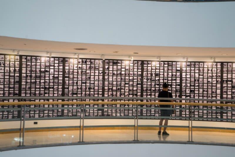 O homem está olhando a fotografia ou a imagem no museu da galeria fotografia de stock