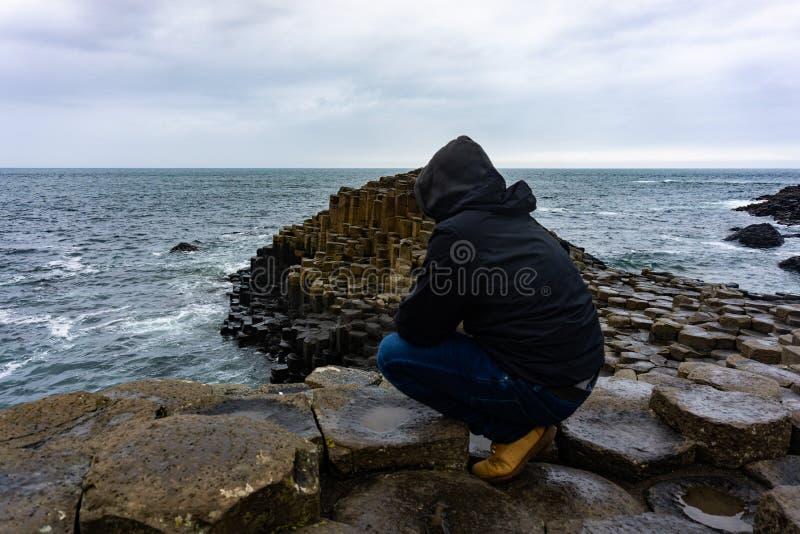 O homem está olhando o Oceano Atlântico na calçada do gigante em Irlanda do Norte imagem de stock royalty free
