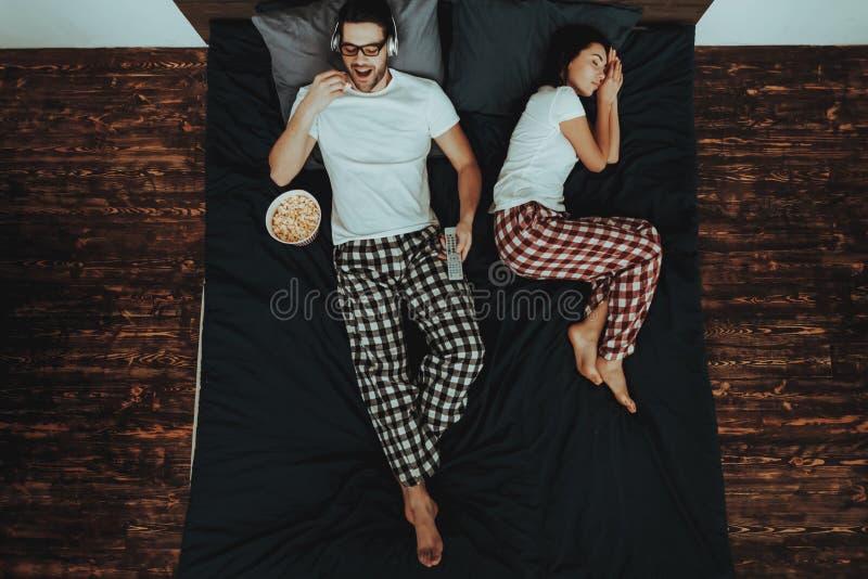 O homem está olhando o vídeo e a mulher que dormem na cama foto de stock royalty free