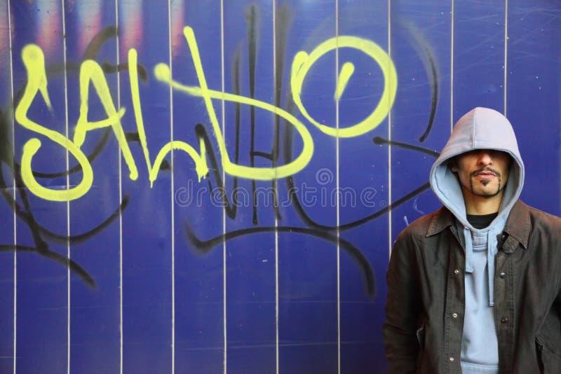 O homem está permanecendo a parede próxima com grafittis em uma rua imagens de stock