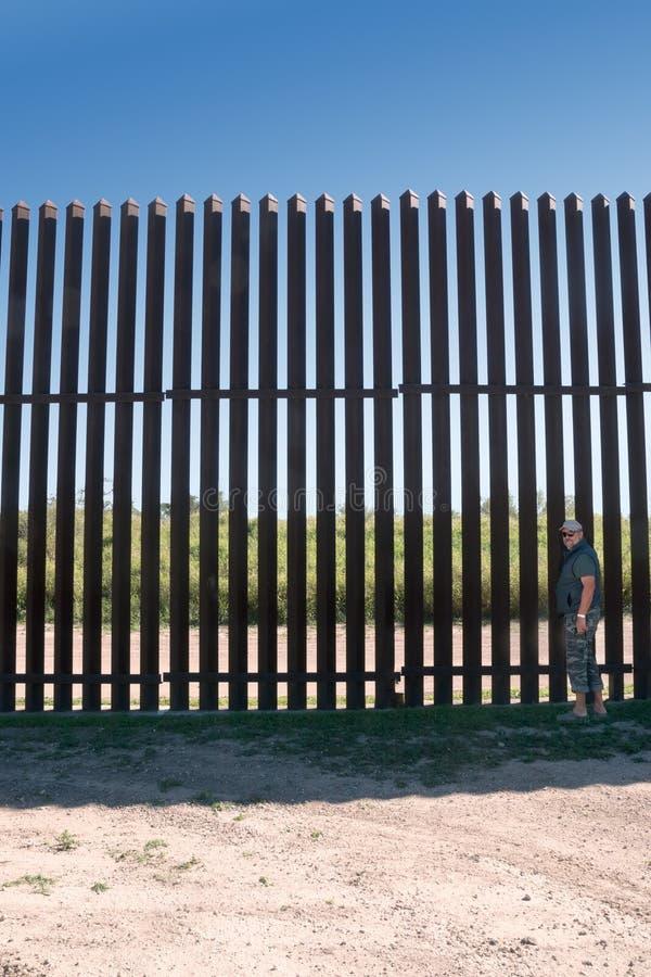 """O homem está perto barreira Estados Unidos de um Mexico†novo do ferro do """"no campo Texas imagem de stock royalty free"""