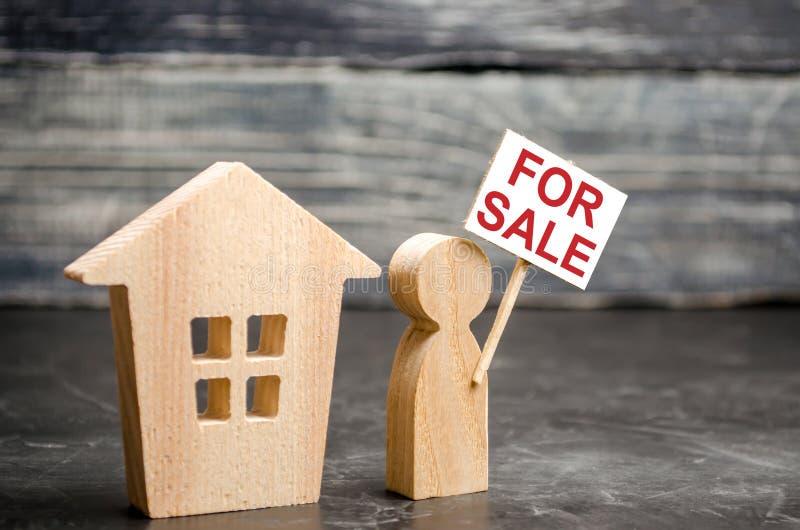 o homem está perto da casa com um cartaz para a venda anunciando e atraindo compradores Vendendo uma propriedade da casa e dos be fotos de stock royalty free