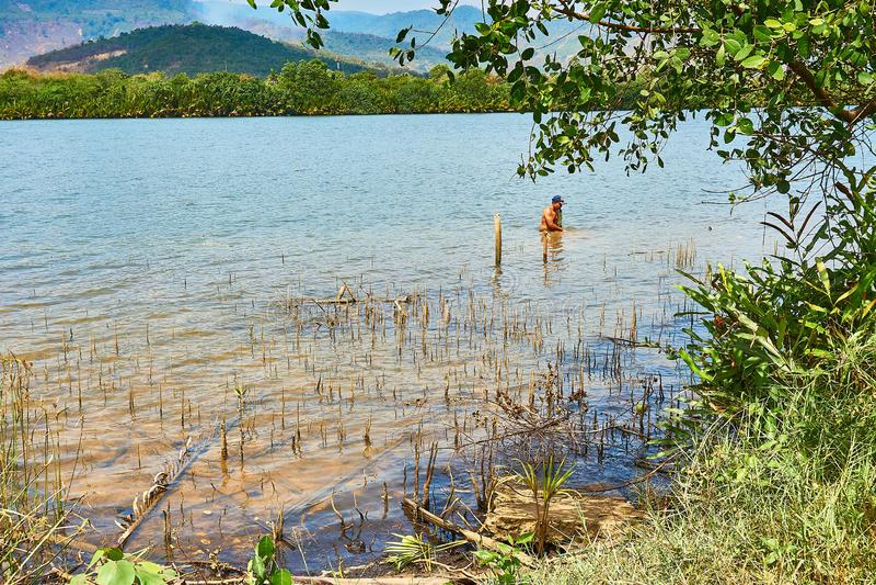 O homem está pescando em Kampot Camboja no rio com as montanhas no fundo imagem de stock royalty free