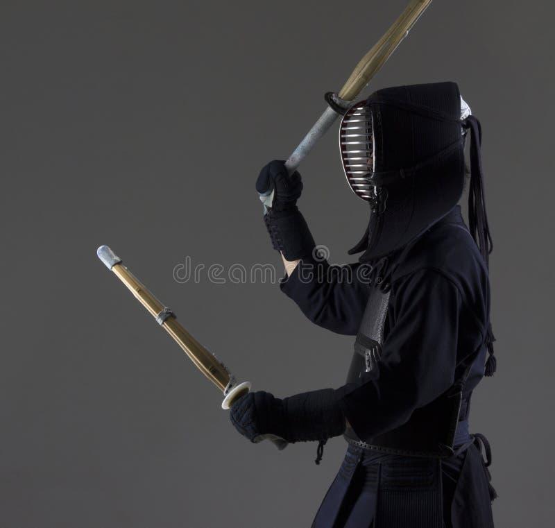 O homem está praticando o kendo na armadura tradicional Ele que balança com as duas espadas de bambu fotografia de stock