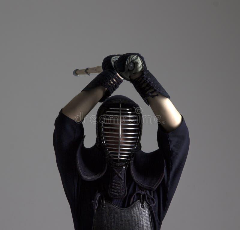 O homem está praticando o kendo na armadura tradicional Ele que balança com espada de bambu fotografia de stock royalty free