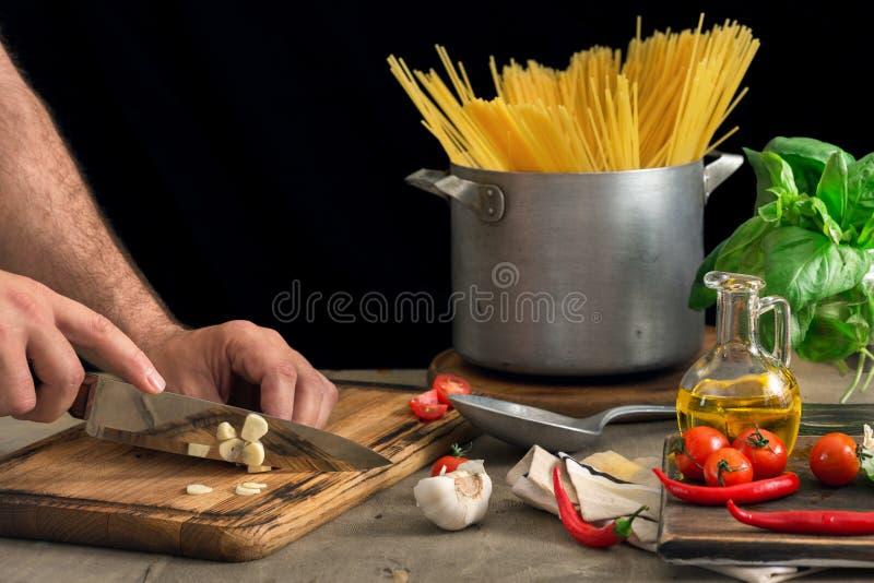 O homem está preparando a massa italiana em uma tabela de madeira imagens de stock