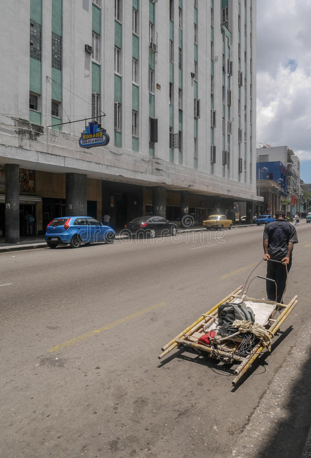 O homem está puxando a construção de madeira em Havana Cuba foto de stock