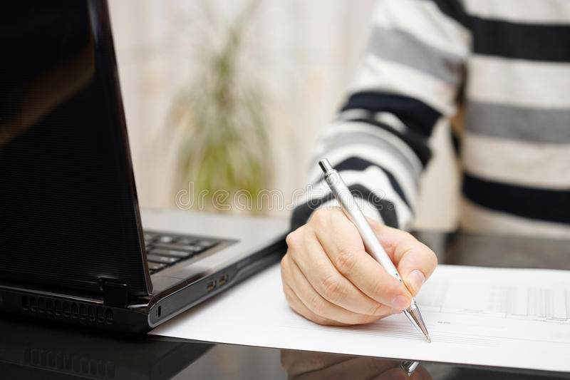 O homem está redigindo o original ou está estudando-o com um portátil ao lado em casa fotografia de stock
