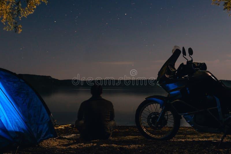 O homem est? sentando-se apenas na praia na escurid?o e a barraca de acampamento dos azul-c?u do othe do olhar iluminou para dent fotografia de stock