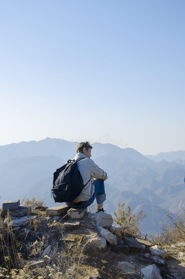 O homem está sentando-se no pico da montanha e está olhando-se na distância às montanhas fotografia de stock