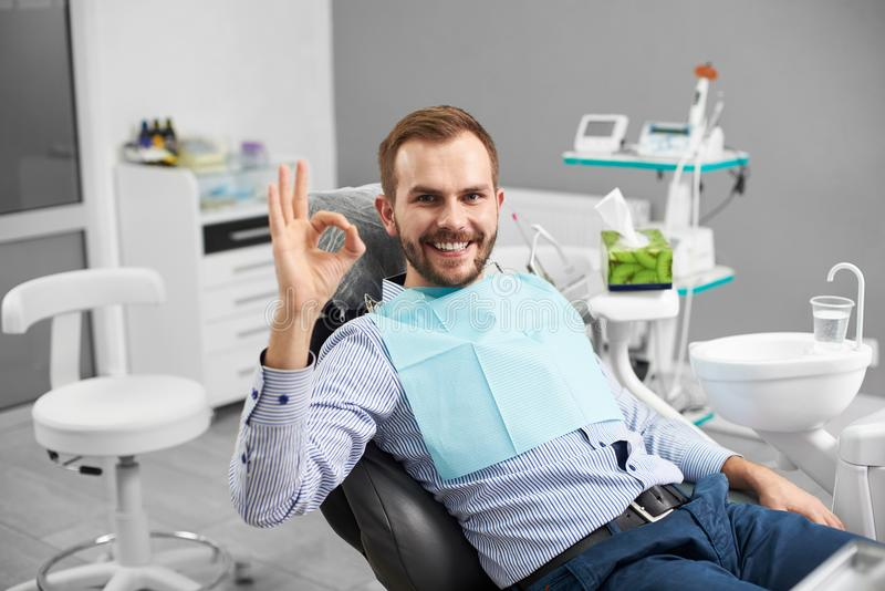 O homem está sorrindo à câmera e está mostrando o sinal aprovado que está sendo satisfeito após o tratamento dos dentes em uma od imagens de stock