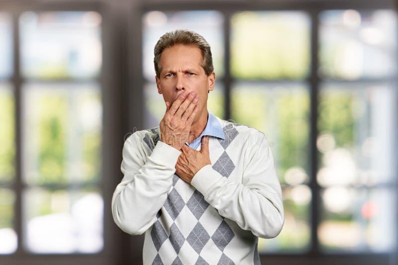 O homem está tendo a tosse no fundo borrado fotografia de stock royalty free
