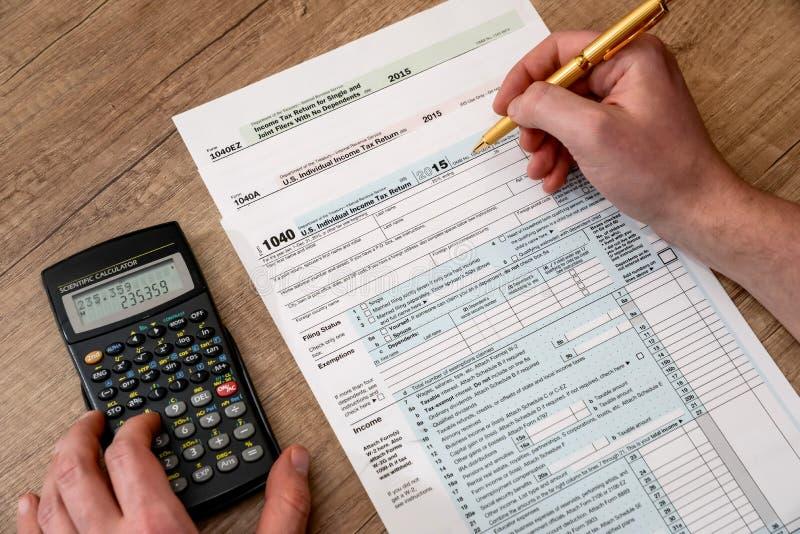 O homem está terminando o formulário de imposto imagem de stock royalty free