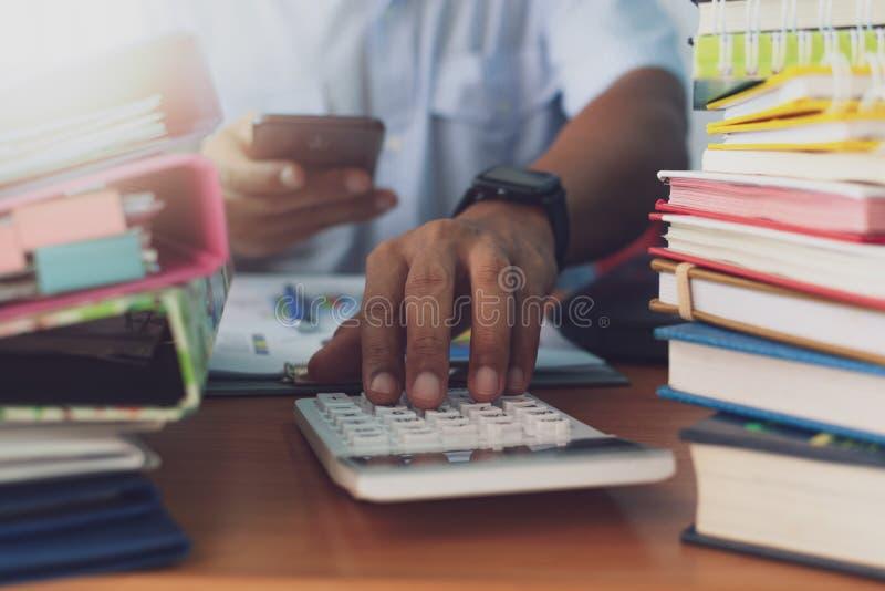 O homem está usando a calculadora e está trabalhando com a pilha de documentos na mesa de escritório foto de stock