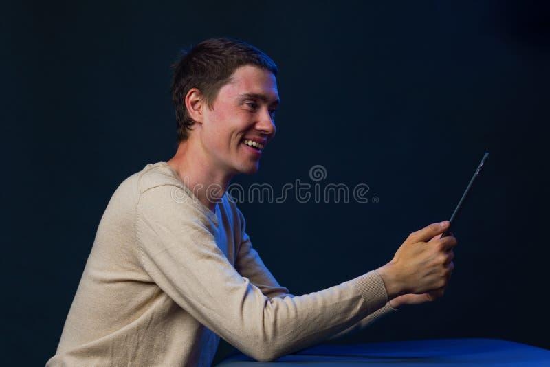 O homem está usando o tablet pc para uma comunicação no bate-papo ou no bate-papo video Conceito social dos media fotografia de stock