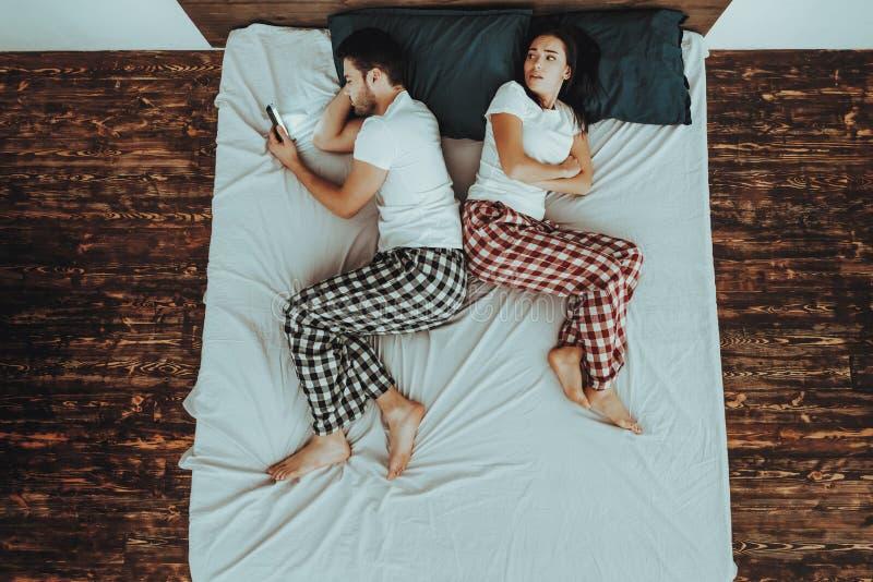 O homem está usando o telefone celular e a mulher que encontram-se na cama fotografia de stock royalty free