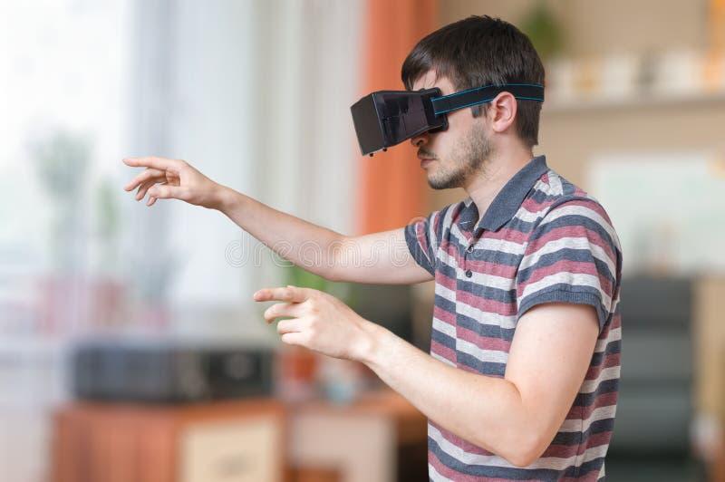 O homem está vestindo vidros do vr e está tocando em algo imagem de stock royalty free