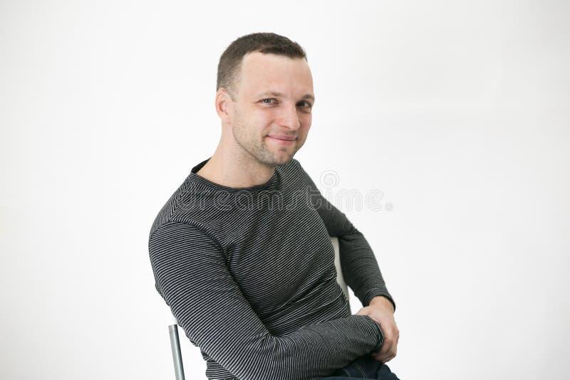 O homem europeu adulto novo está sentando-se na cadeira imagens de stock royalty free